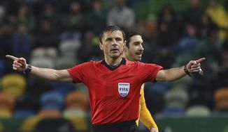 FILE - In this Thursday, April 12, 2018 file photo, referee Milorad Mazic gestures during the Europa League quarterfinal second leg soccer match between Sporting CP and Atletico Madrid at the Alvalade stadium in Lisbon. UEFA has picked two World Cup referees for its club competition finals before the tournament in Russia. UEFA says Milorad Mazic of Serbia will referee the Champions League final between Liverpool and Real Madrid on May 26 in Kiev. Bjorn Kuipers of the Netherlands will referee the Atletico Madrid-Marseille Europa League final May 16 in Lyon. (AP Photo/Armando Franca, File)
