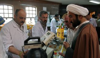 In this May 2, 2006, file photo, Iranian technicians explain a piece of equipment to a clergyman during an exhibition of Iran's Atomic Energy Organization at the Qom University in Qom, Iran. Iran's nuclear deal with world powers faces its biggest diplomatic challenge yet as President Donald Trump appears poised to withdraw the U.S. from the accord. (AP Photo/Vahid Salemi, File)