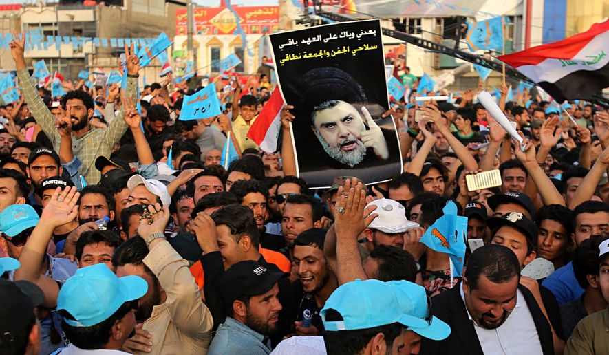 In this Friday, May 4, 2018 photo, followers of Shiite cleric Muqtada al-Sadr, seen in poster, take part in a parliamentary campaign rally in Baghdad, Iraq. Voters head to the polls next weekend for the first time since the government declared victory against the Islamic State group, in elections that could tilt the balance of power between the United States and Iran. The atrocities committed by IS against fellow Sunnis, and the national campaign against the extremist group, seem to have eased the sectarian tensions that marked past votes. (AP Photo/Karim Kadim)