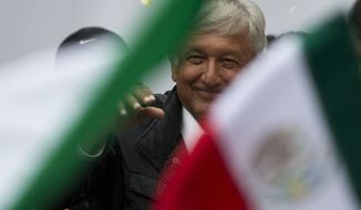 Presidential candidate Andres Manuel Lopez Obrador of the MORENA party waves as supporters hold up Mexican flags, during a campaign rally in the Benito Juarez district of Mexico City, Monday, May 7, 2018. Mexico will choose a new president in general elections on July 1. (AP Photo/Rebecca Blackwell)