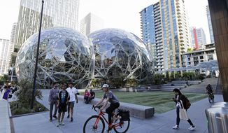 In this Monday, May 7, 2018, photo, pedestrians and cyclists gather near the Amazon Spheres, in Seattle. Seattle's latest tax proposal to combat homelessness takes aim at large businesses such as Amazon that have helped drive the city's economic boom. But businesses and others say the so-called head tax is misguided and potentially harmful and they question whether the city is effectively using the tens of millions of dollars it already spends on homelessness each year. (AP Photo/Ted S. Warren)