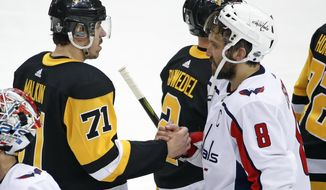 Washington Capitals' Alex Ovechkin (8) shakes hands with Pittsburgh Penguins' Evgeni Malkin (71) after the Capitals' 2-1 overtime win in Game 6 of an NHL second-round hockey playoff series in Pittsburgh, Monday, May 7, 2018. The Capitals won the series, four games to two. (AP Photo/Gene J. Puskar)