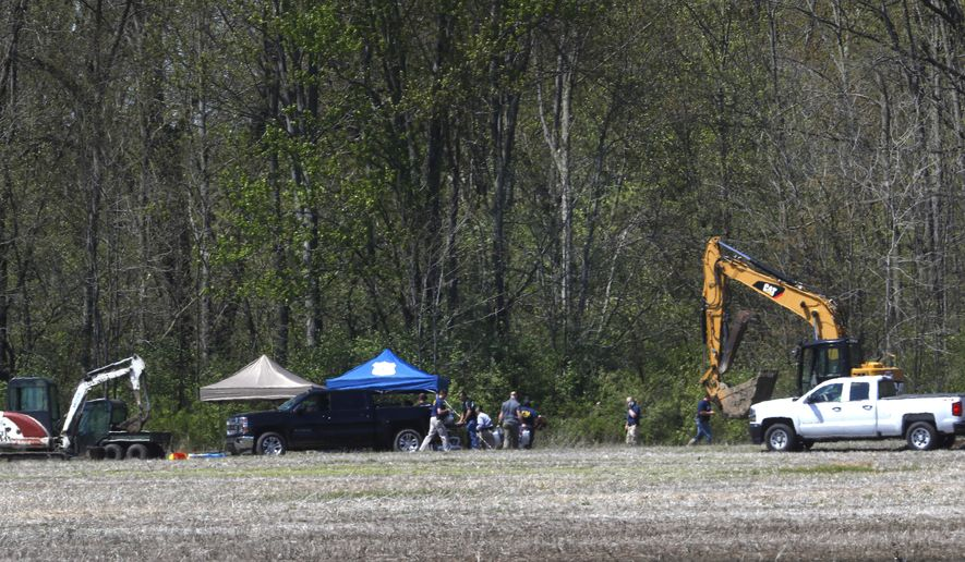 Authorities work near a rural wooded area in Macomb Township, Mich., Tuesday, May 8, 2018. Authorities excavating woods in southeastern Michigan, about 30 miles from downtown Detroit, for the remains of a 12-year-old girl last seen in 1979, also could be looking for the bodies of up to half a dozen others who have been reported missing over the years. The search started Monday for the remains of Kimberly King, but Warren Police Commissioner Bill Dwyer said there could be others buried in the area. (AP Photo/Paul Sancya)