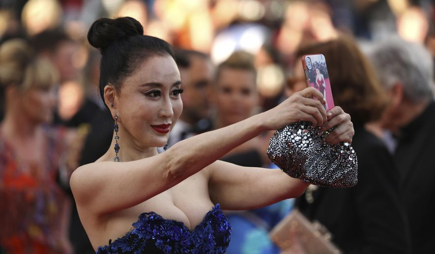 A guest takes a selfie photograph upon arrival at the opening ceremony of the 71st international film festival, Cannes, southern France, Tuesday, May 8, 2018. (Photo by Vianney Le Caer/Invision/AP)