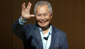"""Actor George Takei, best known for his role as Hikaru Sulu on the television series """"Star Trek,"""" greets the audience before speaking about his experiences in U.S. internment camps during World War II, at an appearance at Boston Public Library, Tuesday, May 8, 2018, in Boston. Takei used his family's story as the inspiration for the Broadway musical """"Allegiance."""" (AP Photo/Steven Senne)"""