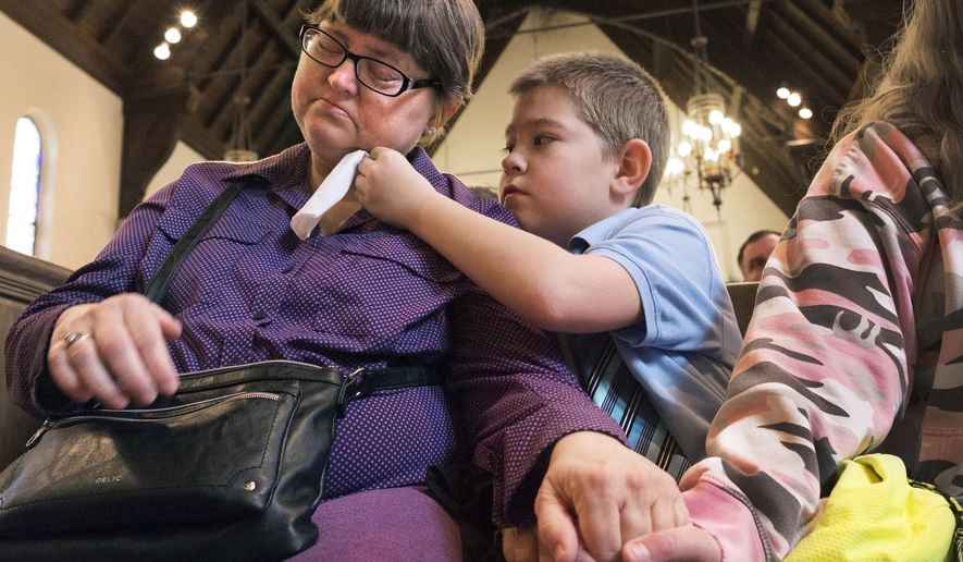FILE - In this April 20, 2018, file photo provided by Steve Bohnstedt, Nicholas Weible offers his mom, Wendy Smith, a tissue during the memorial service for his father, Christopher Weible, held at First Christian Church in Quincy, Ill. Adams County Coroner James Keller is facing sharp criticism for how he handles poor people who can't afford to bury their loved ones. Susana Mendoza, the Illinois state comptroller, denounced the county coroner's practice of holding remains Tuesday, May 8, 2018. (Steve Bohnstedt via AP, File)