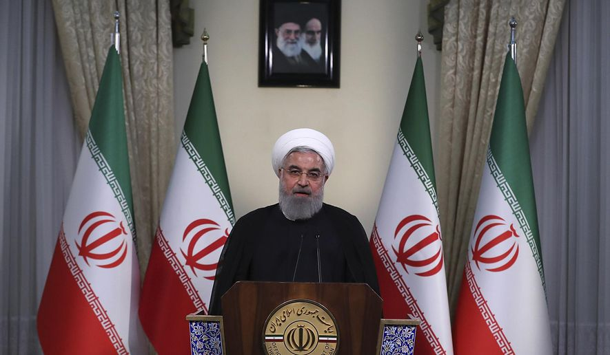 """In this photo released by official website of the office of the Iranian Presidency, President Hassan Rouhani addresses the nation in a televised speech in Tehran, Iran, Tuesday, May 8, 2018. Iranian President Hassan Rouhani said Tuesday he'd send his foreign minister to negotiate with countries remaining in the nuclear deal after Donald Trump's decision to pull America from the deal, warning he otherwise would restart enriching uranium """"in the next weeks."""" (Iranian Presidency Office via AP)"""