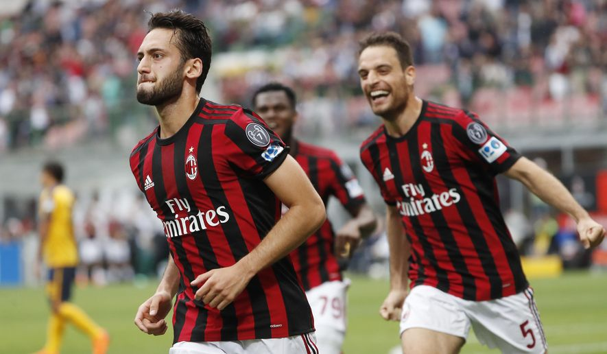 AC Milan's Hakan Calhanoglu, left, celebrates with his teammate Giacomo Bonaventura, right, after scoring his side's opening goal during the Serie A soccer match between AC Milan and Hellas Verona at the San Siro stadium in Milan, Italy, Saturday, May 5, 2018. (AP Photo/Antonio Calanni)
