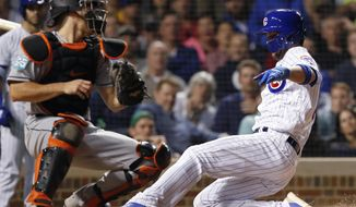 Chicago Cubs' Kris Bryant, right, slides safely into home plate to score the go-ahead run against Miami Marlins' J.T. Realmuto during the eighth inning of a baseball game Tuesday, May 8, 2018, in Chicago. (AP Photo/Jim Young)