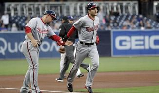 Washington Nationals' Trea Turner, right, is greeted by third base coach Bob Henley after hitting a home run during the first inning of a baseball game against the San Diego Padres Monday, May 7, 2018, in San Diego. (AP Photo/Gregory Bull)