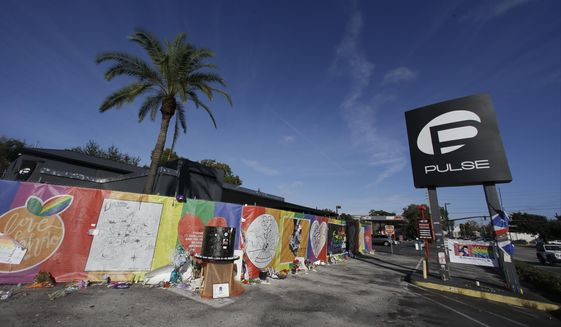 In this Nov. 30, 2016, file photo, artwork and signatures cover a fence around the Pulse nightclub, scene of a mass shooting, in Orlando, Fla. An interim memorial for the 49 people killed at the nightclub is opening to the public on Tuesday, May 8, 2018. The onePULSE Foundation said that the temporary memorial will open at 3 p.m., at the site of Pulse nightclub, which has remained closed since the June 2016 shooting. (AP Photo/John Raoux, File)