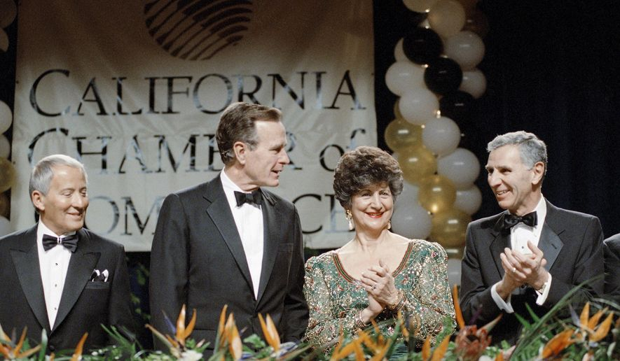 """FILE - In this March 1, 1990 file photo, President George H. Bush receives a round of applause from California Governor George Deukmejian and his wife, Gloria, as Bush was introduced before the California Chamber of Commerce centennial dinner in Los Angeles. A former chief of staff says two-term California governor Deukmejian, whose anti-spending credo earned him the nickname """"The Iron Duke,"""" has died at age 89. Steve Merksamer says Deukmejian died Tuesday, May 8, 2018, of natural causes. (AP Photo/Barry Thumma, File)"""