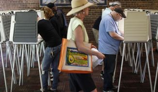 Voters fill out their ballots at the Cincinnati Public Library precinct on primary election day, Tuesday, May 8, 2018, in Cincinnati. Ohio's roller-coaster gubernatorial primary season will be decided Tuesday as Republicans and Democrats vote for their nominees to replace term-limited Republican Gov. John Kasich. (AP Photo/John Minchillo)