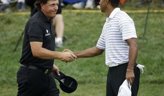 FILE - In this Aug. 8, 2014, file photo, Phil Mickelson, left, shakes hands with Tiger Wood after the second round of the PGA Championship golf tournament at Valhalla Golf Club in Louisville, Ky. Woods and Mickelson are in the same group at The Players Championship this week.   (AP Photo/David J. Phillip, File)