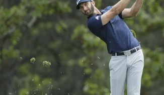 FILE - In this April 8, 2018 file photo Dustin Johnson hits a shot to the first hole during the fourth round at the Masters golf tournament in Augusta, Ga. Johnson has been No. 1 for 15 months and needs his best finish at The Players Championship to have a chance to stay there. (AP Photo/David J. Phillip, file)
