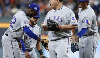 FILE - In this April 15, 2018 file photo Texas Rangers, center, starting pitcher Bartolo Colon is congratulated by team mates Adrian Beltre, Isiah Kiner-Falefa and Ronald Guzman as he leaves the mound to be relieved by Alex Claudio during the eighth inning of a baseball game against the Houston Astros in Houston. No current player in the majors is older than Colon, who turns 45 on May 24, 2018. And no active pitcher has as many as his 241 career wins or 533 starts, the firsts of both which came for Cleveland in 1997. (AP Photo/Michael Wyke)