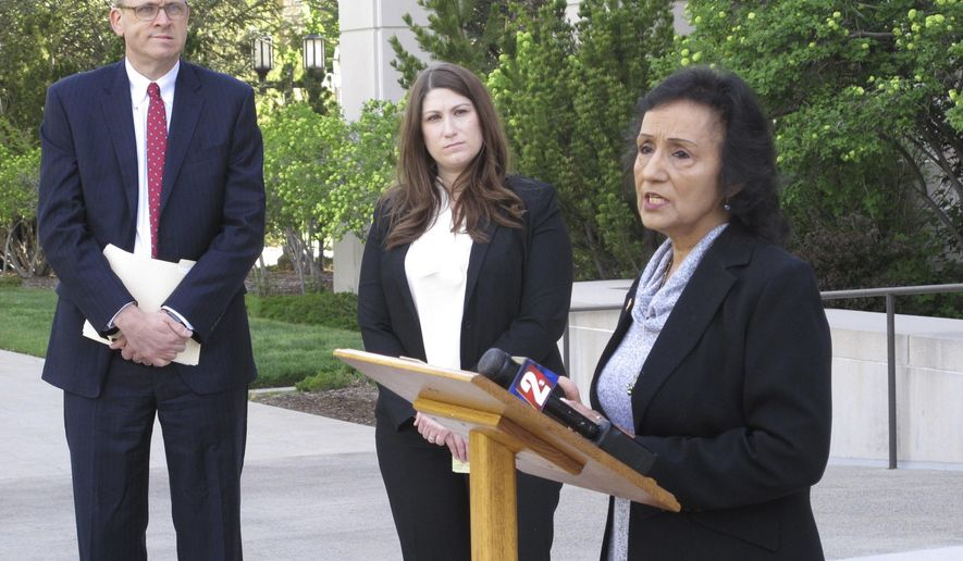 Theresa Navarro, right, a plaintiff in a lawsuit seeking to block what she calls an ''anti-immigrant'' ballot measure, talks to reporters while lawyers for the American Civil Liberties Union Marc Elias, left, and Amy Rose look on outside the Nevada Supreme Court, Tuesday, May 8, 2018, in Carson City, Nev. They urged the court Tuesday to uphold a lower court ruling that would keep off the November ballot an initiative to ban sanctuary cities. (AP Photo/Scott Sonner)