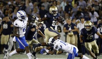 FILE - In this Oct. 7, 2017, file photo, Navy running back Darryl Bonner, top, leaps over Air Force defensive back Robert Bullard in the second half of an NCAA college football game in Annapolis, Md. CBS Sports, Navy and the American Athletic Conference have agreed to a 10-year contract extension through 2027 that will keep television rights to the Midshipmen's home football games with the network. The deal was announced Wednesday, May 9, 2018. (AP Photo/Patrick Semansky, File)
