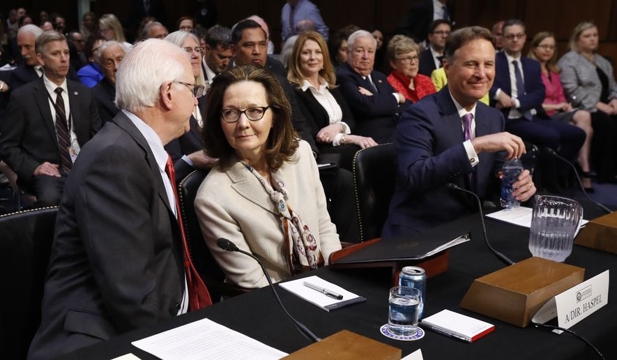 CIA nominee Gina Haspel speaks with Sen. Saxby Chambliss, R-Ga., before being sworn in during a confirmation hearing of the Senate Intelligence Committee, on Capitol Hill, Wednesday, May 9, 2018 in Washington. Sen. Evan Bayh, D-Ind., is seated right. (AP Photo/Pablo Martinez Monsivais)
