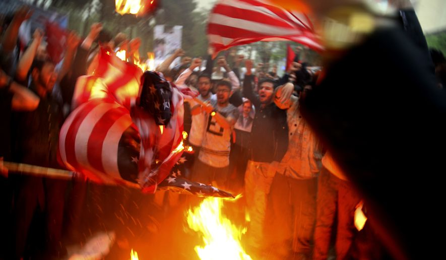 Iranian demonstrators burn representations of the U.S. flag during a protest in front of the former U.S. Embassy in response to President Donald Trump's decision Tuesday to pull out of the nuclear deal and renew sanctions, in Tehran, Iran, Wednesday, May 9, 2018. (AP Photo/Vahid Salemi)