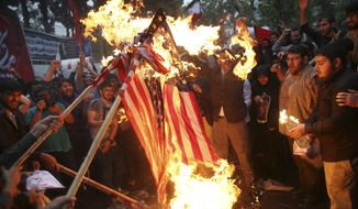 Hardline Iranian demonstrators burn representations of the U.S. flag during a gathering in front of the former U.S. Embassy in Tehran, Iran, Wednesday, May 9, 2018, reacting to President Donald Trump's decision to pull out of the nuclear deal and renew sanctions on Iran. (AP Photo/Vahid Salemi)