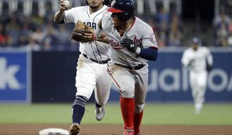 San Diego Padres shortstop Freddy Galvis, left, chases down Washington Nationals' Wilmer Difo during the fifth inning of a baseball game Wednesday, May 9, 2018, in San Diego. Difo was out on the play. (AP Photo/Gregory Bull)