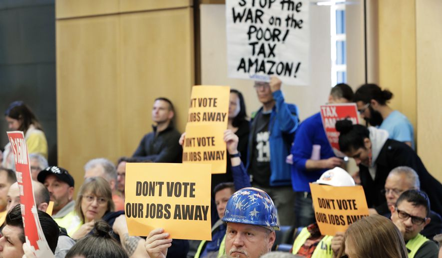"""Jimmy Haun, center, holds a sign that reads """"Don't vote our jobs away,"""" Wednesday, May 9, 2018, as he attends a Seattle City Council committee meeting at City Hall in Seattle where public comment was heard on a controversial proposal to tax large businesses such as Amazon.com to fund efforts to combat homelessness. Haun is the political director of the Pacific Northwest Regional Council of Carpenters. (AP Photo/Ted S. Warren)"""