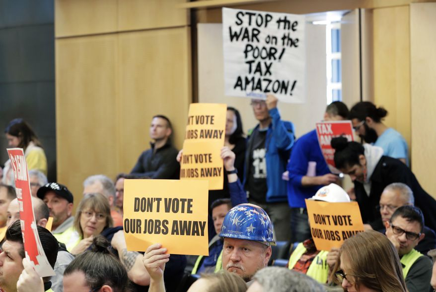 "Jimmy Haun, center, holds a sign that reads ""Don't vote our jobs away,"" Wednesday, May 9, 2018, as he attends a Seattle City Council committee meeting at City Hall in Seattle where public comment was heard on a controversial proposal to tax large businesses such as Amazon.com to fund efforts to combat homelessness. Haun is the political director of the Pacific Northwest Regional Council of Carpenters. (AP Photo/Ted S. Warren)"