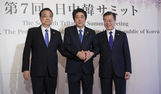 Chinese Premier Li Keqiang, left, Japanese Prime Minister Shinzo Abe, center, and South Korean President Moon Jae-in, right, pose for photographers prior to their summit in Tokyo Wednesday, May 9, 2018. The summit is expected to focus on North Korea's nuclear program and on improving the sometimes-frayed ties among the three northeast Asian neighbors. (AP Photo/Eugene Hoshiko, Pool)