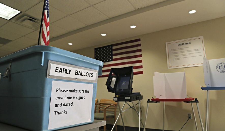 In this March 21, 2016, file photo, an example of an early ballot collection box and demonstration of voting areas is set up ahead of the state's Presidential Primary Election at the Maricopa County Recorder's office in Phoenix. (AP Photo/Ryan Van Velzer, File)