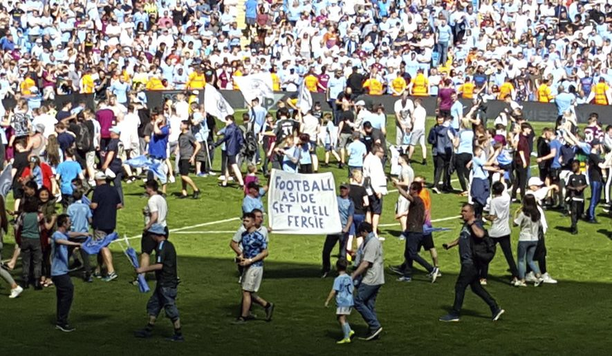 "Manchester City fans hold up a sign reading ""Football Aside Get Well Soon Fergie"" in reference to former Manchester United manager Alex Ferguson after the Premier League match at the Etihad Stadium, Manchester, Sunday May 6, 2018. Manchester United said Saturday May 5, that former manager Alex Ferguson has undergone emergency surgery for a brain haemorrhage. (Andy Hampson/PA via AP)"