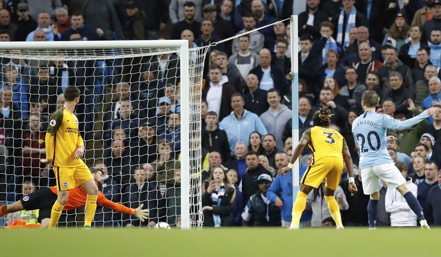 Manchester City's Bernado Silva, right, scores his side's second goal of the game against Brighton & Hove Albion during the English Premier League soccer match at the Etihad Stadium, Manchester, England, Wednesday May 9, 2018. (Martin Rickett/PA via AP)