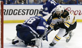 Boston Bruins center Patrice Bergeron (37) tries to stuff the puck past Tampa Bay Lightning goaltender Andrei Vasilevskiy (88) during the third period of Game 5 of an NHL second-round hockey playoff series Sunday, May 6, 2018, in Tampa, Fla. (AP Photo/Chris O'Meara)