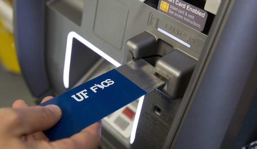 In this April 18, 2018, photo, a detective with the New York City Police Department uses a detection device that indicates if a credit card skimmer is in use at an ATM machine at a New York convenience store. The device is under development by the Florida Institute for Cybersecurity Research. (AP Photo/Mark Lennihan)