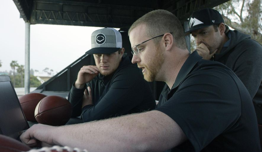 """In this April 19, 2018, photo provided by Wilson Sporting Goods, quarterback Sam Darnold, left, and his mentor, former quarterback Jordan Palmer, right, look on as Wilson Labs engineer Dan Hare explains data gathered from throwing a football using the Wilson Connected Football System, at San Clemente High School in San Clemente, Calif. Darnold, the New York Jets rookie quarterback, was at his old stomping grounds in California last month tossing """"smart"""" footballs equipped with computer chips with Palmer, that were calculating his every throw. (Wilson Sporting Goods via AP)"""