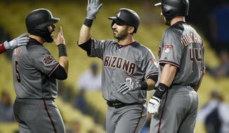 Arizona Diamondbacks' Daniel Descalso, center, celebrates with Alex Avila, left, and Paul Goldschmidt after hitting the go-ahead three-run home run during the 12th inning of a baseball game against the Los Angeles Dodgers in Los Angeles, Tuesday, May 8, 2018. (AP Photo/Kelvin Kuo)