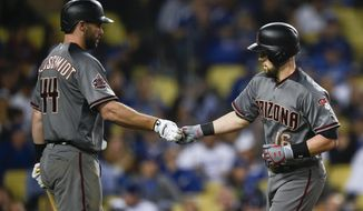 Arizona Diamondbacks' Chris Owings, right, celebrates with Paul Goldschmidt after hitting a solo home run during the third inning of a baseball game against the Los Angeles Dodgers in Los Angeles, Tuesday, May 8, 2018. (AP Photo/Kelvin Kuo)
