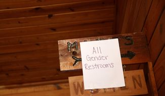 """In this April 28, 2018 photo, an """"all gender"""" sign is taped to the women's restroom during the Black Trans Advocacy Coalition's Family Picnic at Circle R Ranch in Flower Mound, Texas. (Rose Baca/The Dallas Morning News via AP)"""