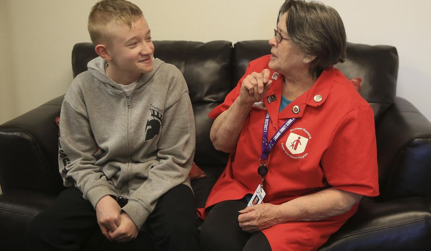 "Dorothyann ""Dot"" Basse talks with freshman Braydon Nelson of Cheyenne's Triumph High on Wednesday, May 2, 2018, at the school. Basse serves in the Foster Grandparent Program and acts as a grandmother for Nelson. She said the experience helps her have the satisfaction of caring for children when she is no longer caring for her biological grandchildren. (Blaine McCartney /The Wyoming Tribune Eagle via AP)"