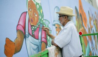 In this Friday, May 4, 2018 photo,  Leo Tanguma adds highlights to a figure on a mural that Tanguma originally painted in 1974 on Canal Street in Houston. (Elizabeth Conle/Houston Chronicle via AP)