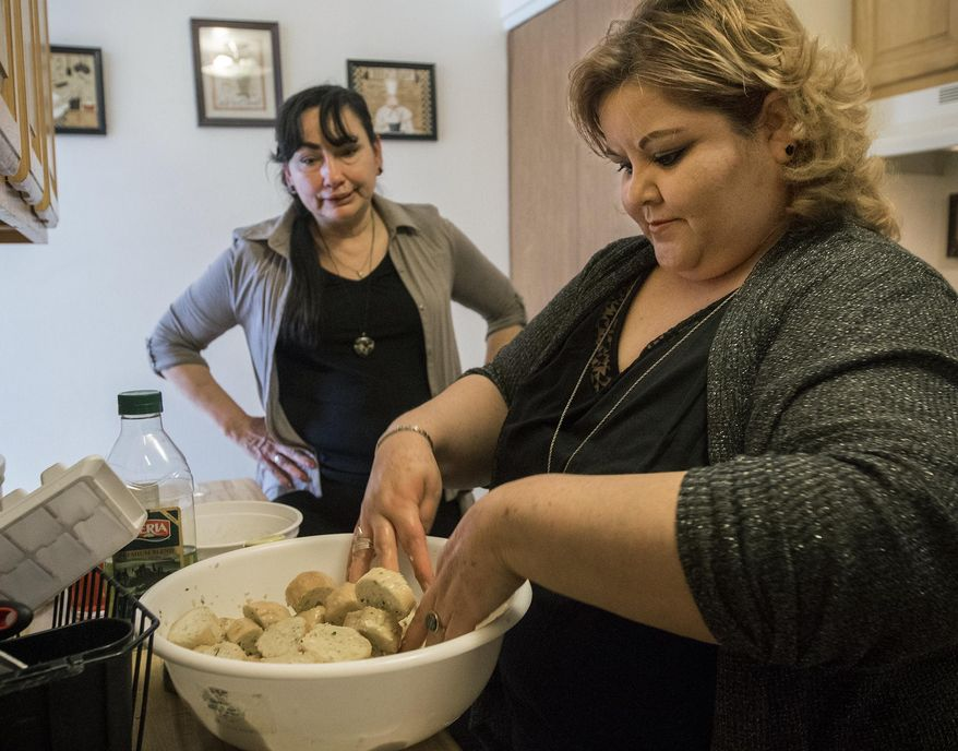 In this April 27, 2018 photo, Teresa Vargas mixes baguette bread and butter for the pasta dinner Howlett is showing her how to make at Vargas's apartment in Gillette, Wy. Howlett is a registered and trained companion through the statewide Wyoming Senior Companion Program through which she is able to help care for Vargas and her daughter. (Rhinna Gelhart/Gillette News Record via AP)