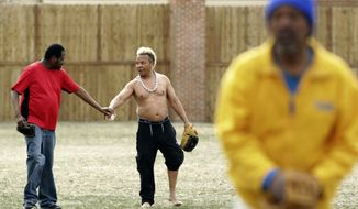 In this Wednesday, April 11, 2018 photo, JoJo Friesan, left, slaps hands with Carlos Rojas, 52, as they work on fielding during practice for a new homeless softball team at Reynolds Park in Madison, Wis. (Amber Arnold/Wisconsin State Journal via AP)