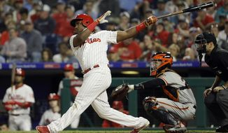 Philadelphia Phillies' Maikel Franco follows through on a home run off San Francisco Giants starting pitcher Chris Stratton during the fourth inning of a baseball game Wednesday, May 9, 2018, in Philadelphia. At center is catcher Buster Posey. (AP Photo/Matt Slocum)