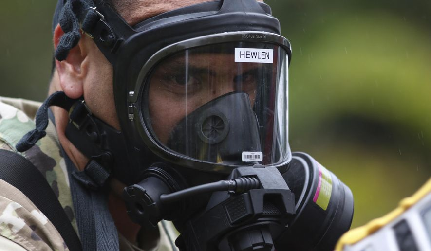 First Lt. Aaron Hew Len, of the U.S. National Guard, tests air quality near cracks that are emitting toxic gasses from a lava flow in the Leilani Estates subdivision near Pahoa, Hawaii, Tuesday, May 8, 2018. Scientists confirm that volcanic activity has paused at all 12 fissures that opened up in a Hawaii community and oozed lava that burned 35 structures. Officials warn that hazardous fumes continue to be released from the cracks in the ground. (AP Photo/Caleb Jones)
