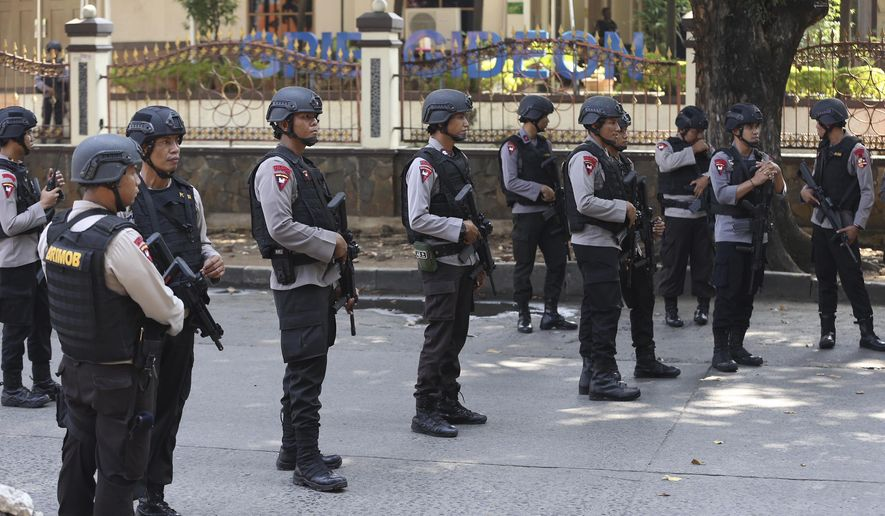 Indonesian Police officers man a roadblock outside the headquarters of elite police force Mobile Brigade, following a prison riot inside the compound in Depok, West Java, Wednesday, May 9, 2018. A riot injured prisoners and some officers at a the police detention center south of Indonesia's capital, police said Wednesday. (AP Photo/Dita Alangkara)