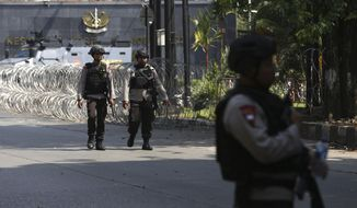 Indonesian Police officers walk past roadblock outside the headquarters of elite police force Mobile Brigade, following a prison riot inside the compound in Depok, West Java, Wednesday, May 9, 2018. A riot injured prisoners and some officers at a the police detention center south of Indonesia's capital, police said Wednesday. (AP Photo/Dita Alangkara)