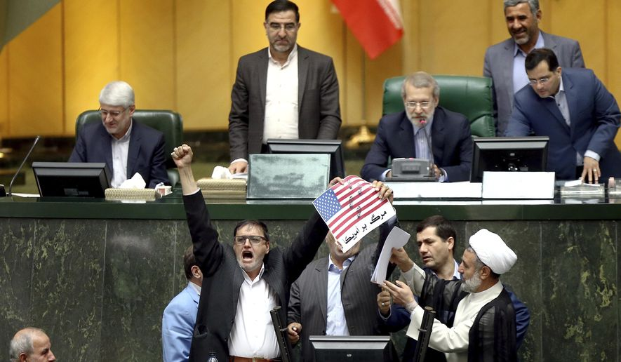 """Iranian lawmakers prepare to burn two pieces of papers representing the U.S. flag and the nuclear deal as they chant slogans against the U.S. at the parliament in Tehran, Iran, Wednesday, May 9, 2018. Iranian lawmakers have set a paper U.S. flag ablaze at parliament after President Donald Trump's nuclear deal pullout, shouting, """"Death to America!"""". President Donald Trump withdrew the U.S. from the deal on Tuesday and restored harsh sanctions against Iran. (AP Photo)"""