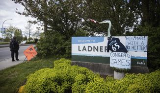 A man walks past a welcome sign bearing a heron adorned with a jersey of Seattle Mariners' pitcher James Paxton, in Ladner, British Columbia, Wednesday May 9, 2018. It didn't take long for locals to honor Paxton after he pitched a no-hitter against the Toronto Blue Jays on Tuesday. By Wednesday morning the welcome sign to the village included handwritten signs congratulating Paxton and a model heron wearing his jersey. (Darryl Dyck/The Canadian Press via AP)