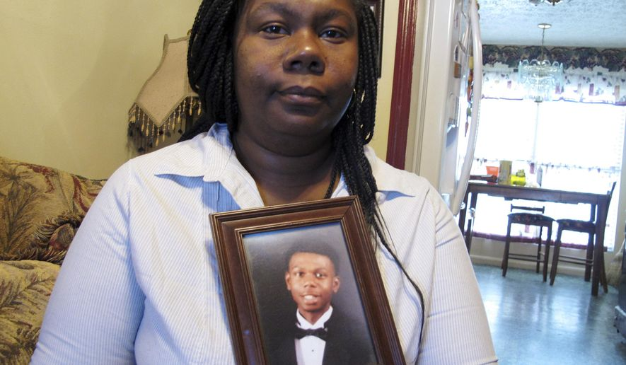 FILE - This April 5, 2018 file photo shows Jameillah Smiley holding a framed photograph of her son, Ricky Boyd, at her home in Savannah, Ga.   Savannah police shot 20-year-old Ricky Boyd outside his home Jan. 23 while trying to arrest him on a murder warrant. The Georgia Bureau of Investigation has said Boyd was holding a BB pistol. Boyd's family insists he was unarmed. Smiley said Wednesday, May 9  that she doesn't trust the local prosecutor to present the case to a grand jury.  (AP Photo/Russ Bynum, File)