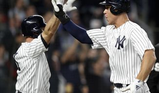 New York Yankees' Aaron Judge, right, celebrates with Brett Gardner after the pair scored on Giancarlo Stanton's double during the third inning of a baseball game against the Boston Red Sox in New York, Wednesday, May 9, 2018. (AP Photo/Kathy Willens)